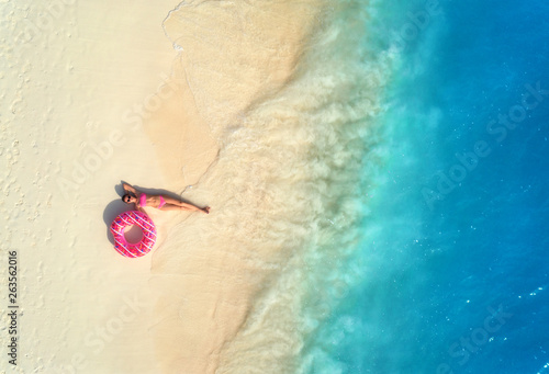 Fotografie, Obraz  Aerial view of the beautiful young lying woman with pink donut swim ring on the white sandy beach near blue sea with waves at sunset