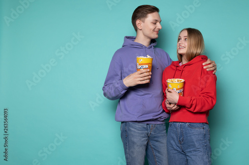 Photo  Photo of cute young couple in casual clothes with popcorn in hands