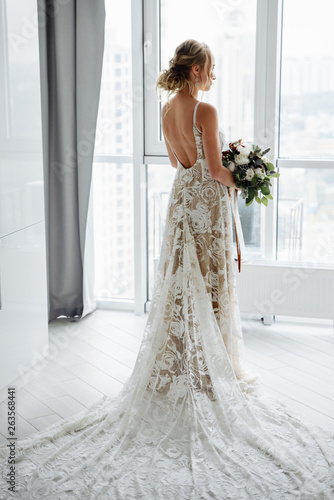 Carta da parati Gorgeous bride in a luxurious long dress with a bouquet in hand, stands and look