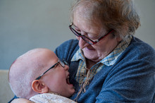 Elderly Woman Sits And Plays With Her Grandson On Couch. Child Is Very Fond Of Grandmother. Boy Kiss And Hug His Beloved Grandmother. Kid Shows Him Playing On Rocking Horse.