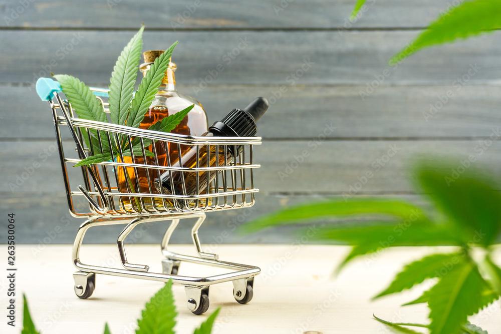 Fototapeta Supermarket trolley with marijuana leafs and medical cannabis oil cbd on wooden backdrop