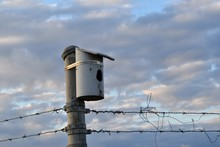 Metal Birdhouse On A Chainlink Fence With Barbed Wire With A Cloudy Sky In The Background, Is Very Industrial And Stark.