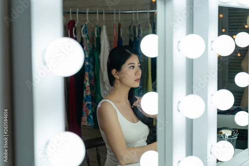 side view of beautiful chinese female actress reflection sitting at makeup table looking in mirror with bulbs fixing hair hand touching soft as brush comb in dressing room Canvas Print
