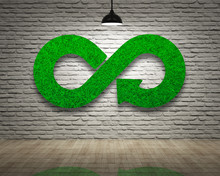 Green Eco-friendly And Circular Economy Concept. Infinity Arrow Recycling Symbol Of Green Grass Texture On Bricks Wall With Ceiling Lamp Of White Light And Wooden Floor.