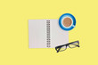 One transparent optical glasses in black plastic frame near paper notepad with blank sheets and full cup of coffee on table of yellow color. Top view. Business concept. Copy space for your text