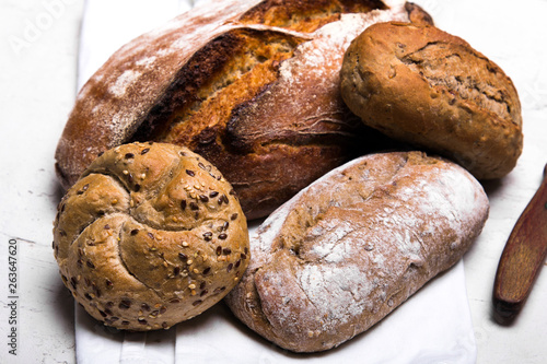 Foto op Plexiglas Bakkerij Tasty dark bread and buns on white background, copy space. Bakery products, wholemeal bread and brown whole wheat buns