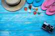 Flat lay design of travel to the sea concept with camera, hat, sandals and shell on blue wooden background.