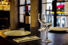 Empty Wine Glasses And A Bottle Of Wine. Empty White Plate With Fork And Knife On  Wooden Table Close To Window