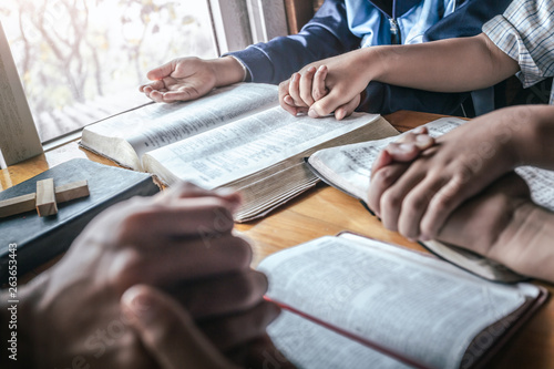 Fotografie, Tablou  Christian group praying together around table at home, prayer meeting concept