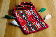 Ethnic Patterned Red Saddlebag Sack On Wooden Background Close Up View