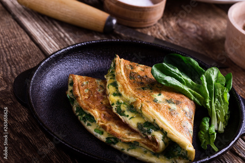 Spinach omelette in cast iron skillet, healthy vegetarian breakfast