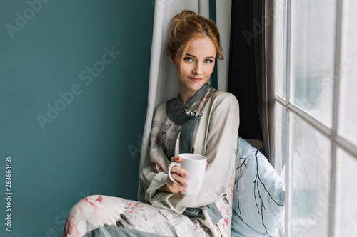Photo sur Aluminium Cafe Pretty young woman sitting on window sill with mug of coffee, tea in her hand, morning relax. Turquoise wall on background. Wearing silk pajamas in flowers, light makeup, pure beauty.