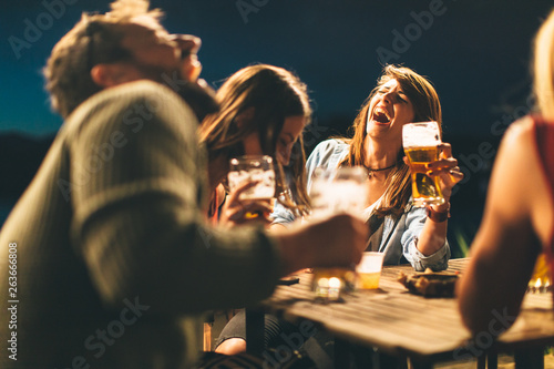 Canvas Print Group of friends drink beer on the terrace during summer night
