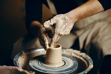 Man Potter Working On Potters Wheel Making Ceramic Pot From Clay In Pottery Workshop