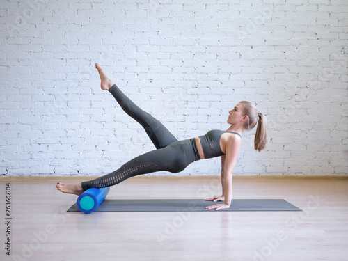 Fototapeta Caucasian young woman in grey sports suit doing pilates workout on math with fit