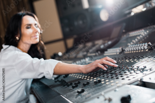 selective focus of attractive sound producer working on mixer console - 263670401