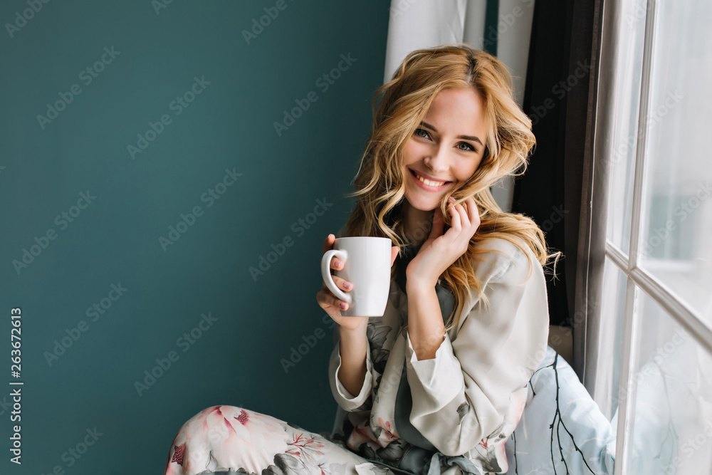Fototapeta Cheerful blonde woman relaxing and sitting on window sill, holding cup of coffee, tea. She has long blonde wavy hair, beautiful smile. Wearing nice pajama in flowers.
