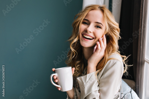 Photo sur Toile The Young woman talking phone and laughing with cup of coffee, tea in hand, happy morning. She has beautiful wavy blonde hair. Room with blue, turquoise wall on background. Wearing nice lace pajama.