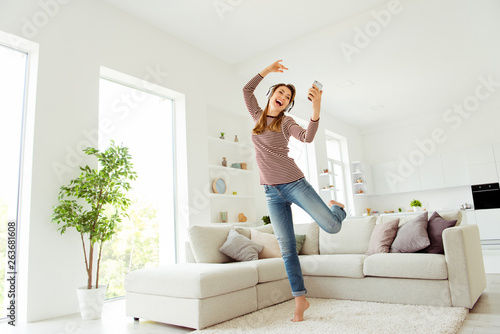 Full length body size photo beautiful she her model lady hands telephone read words earflaps funky dancing wear jeans denim striped pullover clothes comfort flat couch divan house living room indoors - 263681608
