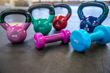 Colrful Kettlebells And  Dumbbell On The Floor In The Gym