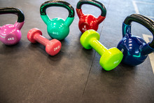 Multi-colour Kettlebells And  Dumbbell On The Floor In The Gym
