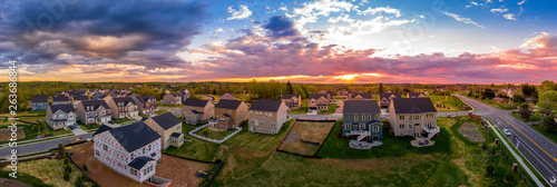 Fototapeta Aerial view of new construction street with luxury houses in a Maryland upper middle class neighborhood American real estate development in the USA with stunning sunset color sky obraz