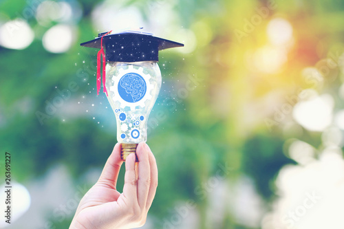 Woman hand holding cog inside in light bulb with graduates hat on natural green Canvas Print