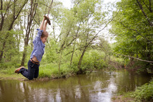 Cute Boy Rides A Homemade Bungee In The Park. Bungee Tied To A Tree Branch On The River Bank. A Happy Child Flies Over The Water On A Bungee. Spring In The Park. Outdoor Activities For Children