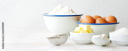 Fototapeta Ingredients for making dough, dessert on white wooden table. Flour, butter, sugar, eggs ingredients obraz