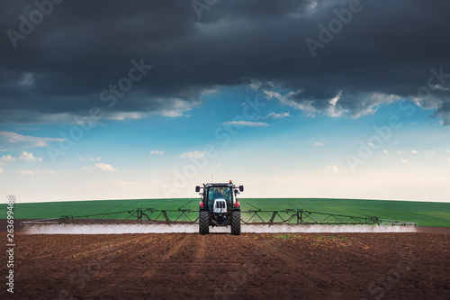 Fotomural Farming tractor plowing and spraying on field