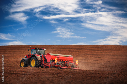 Farmer with tractor seeding crops at field Canvas