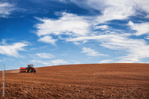 Fotografía Farmer with tractor seeding crops at field