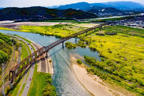 菜の花の咲き誇る高梁川河川敷の春と鉄橋の風景が美しい
