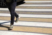 Pedestrian Crossing The Road At A Crosswalk In Front Of The Car. Man Walking On Zebra Marking, Male Legs On The Street, Traffic Violation And Accident Concept