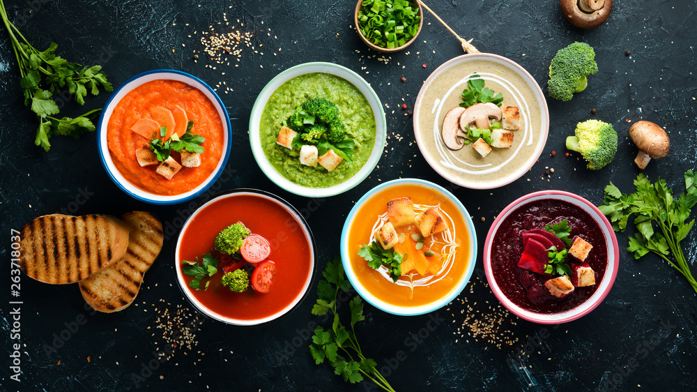 Fototapety, obrazy: Assortment of colored vegetable cream soups. Dietary food. On a black stone background. Top view. Free copy space.