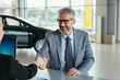businessman shaking hands with sell agent in car showroom