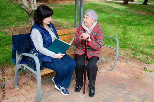 Older woman loves going for a walk with her female caregiver to the park and read books there Fototapet