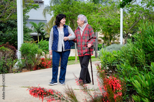 Obraz na plátne Cheerful female carer and an older woman with a walking stick stroll in a city park