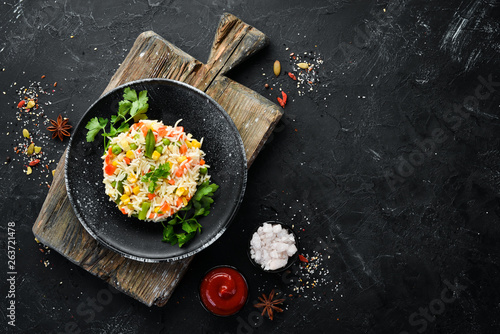 Garden Poster Personal Boiled rice and vegetables. Risotto In a black plate. Top view. Free copy space.