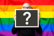 A Man In A White Shirt And Jacket Holding A Sign With A Question Mark On The Background Of The LGBT Flag. The Concept Of Uncertainty In Sexual Orientation, The Attitude Towards Sexual Minorities.