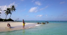 Man Fishes On Beach While Woman Sunbathes On Tropical Island, Aerial Push In 4k