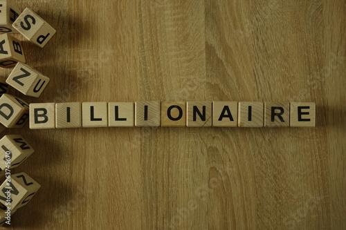 Billionaire word from wooden blocks on desk Wallpaper Mural