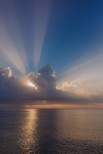Beautiful Amazing Sunrise At Summer Beach. Long Sunrays Seen Behind Fluffy Huge White Clouds Isolated On Blue Sky Background. Vertcial Color Photography.