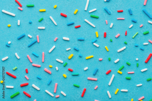 Fotomural colorful sprinkles over blue background, decoration for cake and bakery
