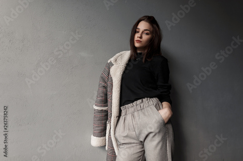 Sexy beautiful young brunette woman in an elegant checkered jacket in a trendy black shirt in stylish gray pants standing near a vintage wall indoors Wallpaper Mural