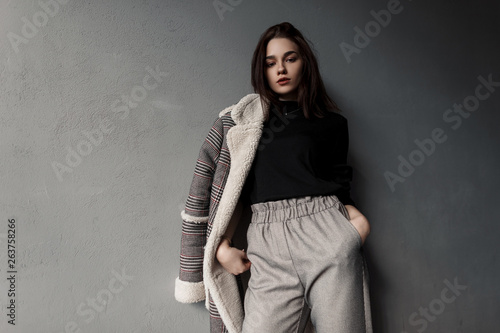 Fotografie, Obraz  Modern stylish young brunette woman in gray elegant pants in a black shirt in a fashionable checkered jacket in retro style posing in a studio in near the vintage wall