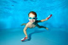 Happy Little Boy Swimming Underwater In The Pool, Smiling And Posing For The Camera With Toys In His Hands On A Blue Background. Portrait. Underwater Photography. Horizontal Orientation