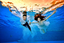 Happy Bride And Groom In Wedding Dresses Swim Underwater On The Background Of A Bright Sunset On The Surface Of The Water. They Smile And Pose For The Camera With Their Arms Outstretched. Portrait