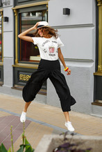 Stylish Young Girl Dressed In A White T-shirt, Black Wide Trousers And White Sneakers Is Jumping In The Street On A Sunny Day
