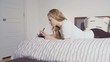 Side view of woman in casual cloths lying on bed, writing thoughts into notebook at home
